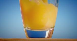 Versamento del vetro di succo d'arancia che crea spruzzata video d archivio