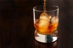 Versamento del vetro di whiskey Fotografie Stock