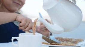 Versamento della cioccolata calda dalla teiera per foggiare a coppa per la bambina stock footage