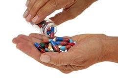 Versamento della miscela delle medicine nella mano su un fondo bianco fotografia stock