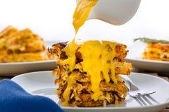 Versamento della salsa di formaggio sopra le patate grattugiate/in padella croccanti Fotografia Stock