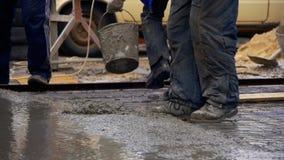 Versamento, ponente calcestruzzo al cantiere facendo uso dei secchi di cemento Movimento lento stock footage