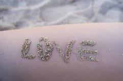 Versanden Sie Aufschriftwörter der Liebe auf der Haut, Sommer, Strand, Ferien stockfoto