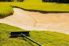 Versanden Sie Bunker-Gefahr und harken Sie auf Golfplatz-Fahrrinne stockfoto