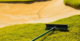 Versanden Sie Bunker-Gefahr und harken Sie auf Golfplatz-Fahrrinne stockfotos