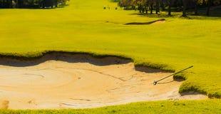 Versanden Sie Bunker-Gefahr und harken Sie auf Golfplatz-Fahrrinne stockfotografie