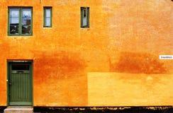 Versanden Sie Farbhausmauer mit der grünen Tür und den Fenstern Stockfotos