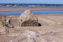 Versanden Sie Skulpturzahlen auf dem Strand am sonnigen Tag lizenzfreies stockbild