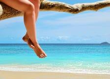 Versanden Sie Strand, azurblaues Meer und Fahrwerkbeine der Frau Stockfotos