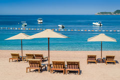 Versanden Sie Strand mit Holzmöbel und vervollkommnen Sie adriatisches Meer Lizenzfreie Stockbilder