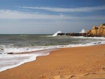 Versanden Sie Strand mit rauen Meereswellen und schönen Sandsteinklippen a Lizenzfreies Stockbild
