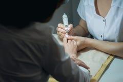 Versandende Nägel des Profesional-Nagel-Technikers mit Maschine stockbild