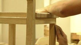 Versandender Holzstuhl des Berufstischlers mit dem Sandpapier, zum der Oberfläche glatt zu machen Lizenzfreie Stockbilder