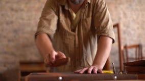 Versandendes Holz des jungen Tischlers in der Werkstatt stock video