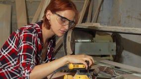 Versandendes Holz des sorgfältigen weiblichen Tischlers an der Werkstatt lizenzfreie stockbilder