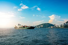 Versandexport versenden industrielle Behälter im Asien-Seeozean in Hong Kong mit Himmelwolken und -wasser; blaue Farbe; Handelsge Lizenzfreies Stockbild
