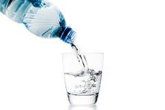 Versando un vetro con la depressione dell'acqua poca bottiglia blu Fotografia Stock