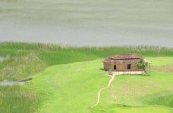 Verschönern Sie mit einer getrennten Hütte, einem Boot und Wasser landschaftlich Lizenzfreie Stockfotografie