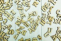 Verschüttete hölzerne Buchstaben auf einem weißen hölzernen Hintergrund lizenzfreie stockfotos