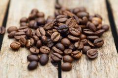 Verschüttete Kaffeebohnen auf einem hölzernen Hintergrund Kaffee Stockfotos