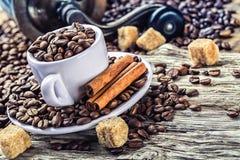 Verschüttete Kaffeebohnen in der Kaffeetasse auf einem sehr alten Holztisch mit Rohrzucker Im Hintergrund eine alte Kaffeemühle Stockfoto