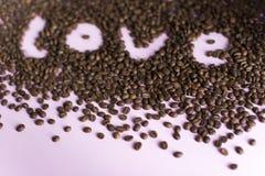 Verschüttete Röstkaffeebohnen mit einer Liebesaufschrift Stockbild