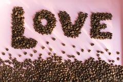 Verschüttete Röstkaffeebohnen mit einer Liebesaufschrift Lizenzfreies Stockbild