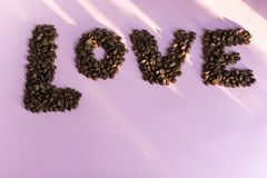 Verschüttete Röstkaffeebohnen mit einer Liebesaufschrift Lizenzfreie Stockfotos