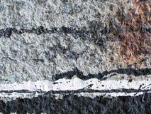 Verschüttete, tropfende Farbe auf einer grauen Wand Stockbild
