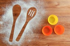 Verschüttetes Mehl auf dem Tisch Löffel-förmiges Impressum in den Mehl- und Kuchenformen lizenzfreies stockfoto