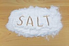 Verschüttetes Salz auf einer hölzernen Tabelle lizenzfreies stockbild