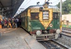 Verschalende Passagiere des indischen Eisenbahnmorgen-Nahverkehrszugs an einer Station Stockbilder