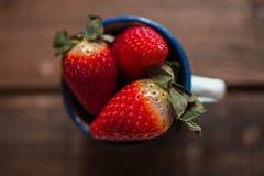 Verscheidene aardbeien in een wit email overvallen op een houten lijst stock fotografie