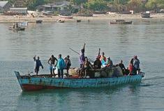 Verscheidene Afrikaanse mensen die in boot langs de kust drijven Royalty-vrije Stock Afbeeldingen
