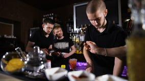 Verscheidene barmannen in modieuze zwarte overhemden, het werk op intensieve wijze stock video