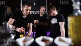Verscheidene barmannen in modieuze zwarte overhemden, het werk op intensieve wijze stock footage