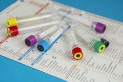 Verscheidene buizen voor bloedmonsters op test verzoeken om blad royalty-vrije stock foto
