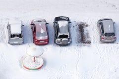 Verscheidene die auto's in straatparkeren met sneeuw na een sneeuwval wordt behandeld Mening van hierboven Stock Foto's
