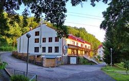Verscheidene drie-verhaal herbergen met heldere muren en rode daken en in een groen bos Stock Foto's