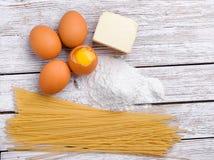 Verscheidene eieren, bloem, de olie en de macaroni liggen op een houten lijst stock afbeelding