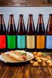 Verscheidene flessen van ambachtbier en snacks op een houten lijst royalty-vrije stock afbeelding