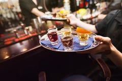 Verscheidene geschotene glazen op zilveren dienblad Stock Foto