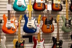 Verscheidene gitaren bij muziekopslag stock afbeeldingen