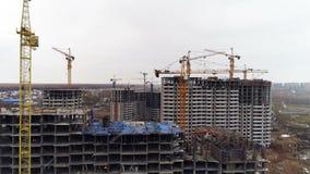 Verscheidene grijze concrete gebouwen met onvolledige hogere vloeren stock video