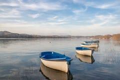 Verscheidene het roeien boten op een kalm meer met blauwe hemel Stock Foto