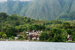 Verscheidene huizen bouwen bij de voet van een berg naast een meer in het Eiland van Sumatra Samosir Stock Afbeelding