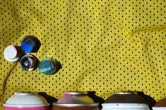 Verscheidene kappen voor de gebruikte die spuitbussen van de aërosolverf liggen op het sportenoverhemd van een basketbalspeler va stock afbeeldingen