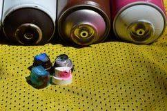 Verscheidene kappen voor de gebruikte die spuitbussen van de aërosolverf liggen op het sportenoverhemd van een basketbalspeler va royalty-vrije stock afbeelding