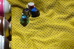 Verscheidene kappen voor de gebruikte die spuitbussen van de aërosolverf liggen op het sportenoverhemd van een basketbalspeler va stock foto