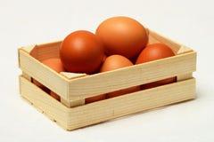 Verscheidene kippeneieren in houten doos Stock Foto